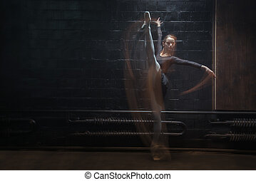 Young gymnast showing her twine on the dark background -...