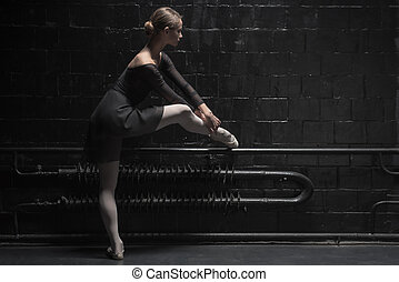 Involved young dancer training near the dark wall -...