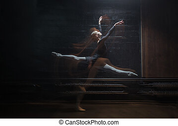 Delighted gymnast jumping on the dark background - Delighted...