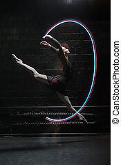 Delighted ballet dancer jumping with a colorful gymnastic...