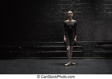 Steady young dancer standing near the dark wall - Ready to...