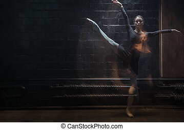 Young gymnast in motion in the dark lighted room - In...