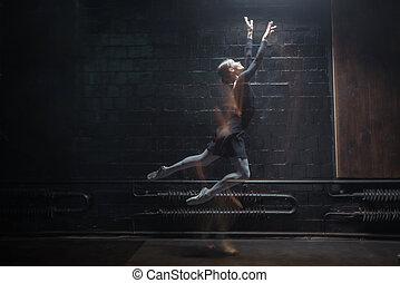 Inspired ballet dancer jumping on the dark background - Full...