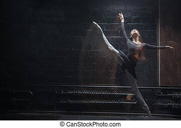 Young gymnast jumping in the twine in the dark room -...