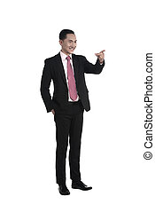 Asian business man pointing something isolated over white...