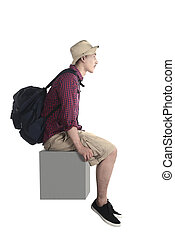 Young tourist sit down on the block isolated over white...