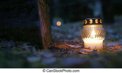 Votive candle on grave, Grave candle. Evening, close-up