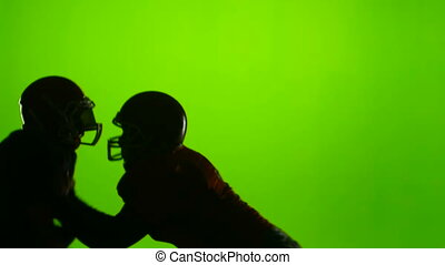 Two football players face each other. Slow motion. Green...