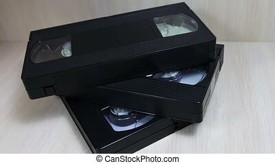 stack of VHS video tape cassette - female hand touches stack...