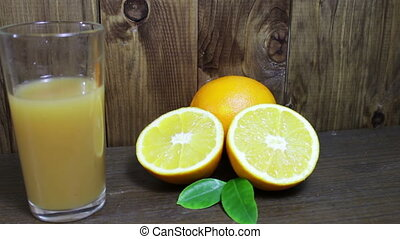 Orange juice in a glass and fresh fruits on wooden...