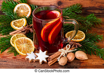 Mulled wine with christmas decoration on wooden background