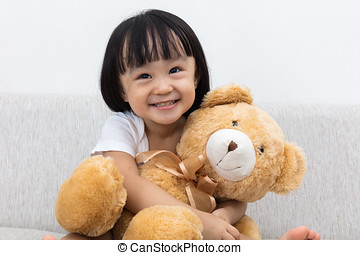 Happy Asian Chinese little girl hugging a teddy bear on the...