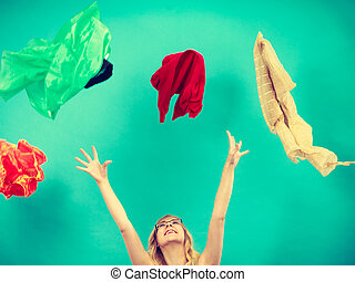 Woman throwing up clothes, clothing flying everywhere -...