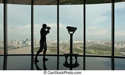 Photographer takes pictures on observation deck in tower Ho...