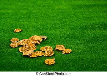 Fake gold coins on green grass
