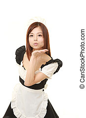 young Japanese woman wearing french maid costume blowing a...
