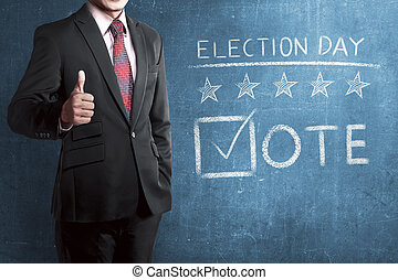 Man with business suit standing beside 'Election Day' writed...