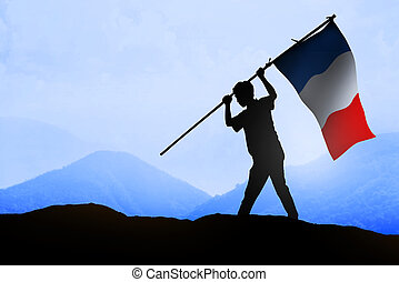 Silhouette of man holding france flag