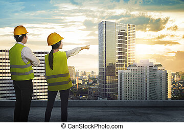 Back view of two architect looking the city from rooftop