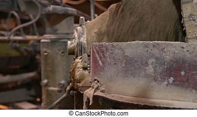 Brick industry. View of sand pours into container - Brick...