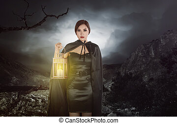 Asian witch woman with a lantern walking on rock hill
