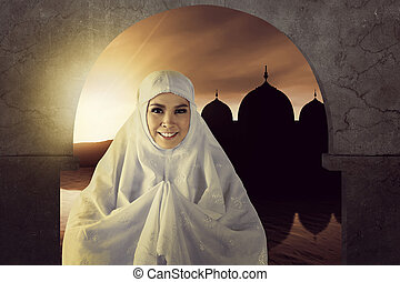 The picture of asian muslim woman pray to god with mosque background