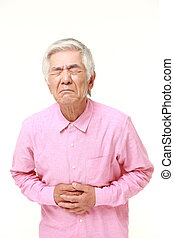 senior Japanese man suffers from stomachache - studio shot...