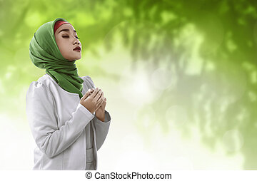 Young asian muslim woman praying to god look seriously and...