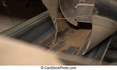 View of sand pours on conveyor belt, close-up