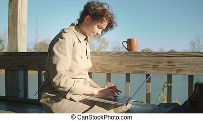 Woman sits on the bench and surfs the internet with laptop