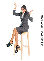 Happy black businesswoman seated on chair.