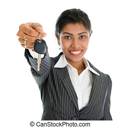 Car dealer - Indian woman showing car key and smiling, focus...