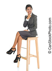Black business woman seated on chair.