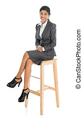 Black businesswoman seated on chair.