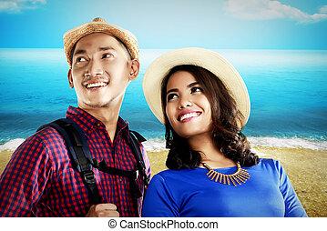 Asian couple travel along on the beach