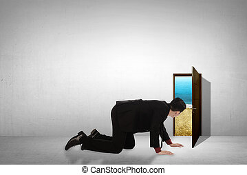 Business man take peek on small door through beach