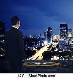 Business man standing on rooftop helipad. Looking at the...