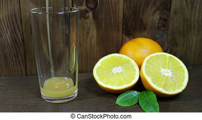 Orange juice in a glass and fresh fruits on wooden background
