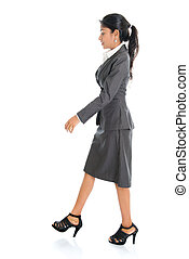 Indian business woman walking - Full length side view of...