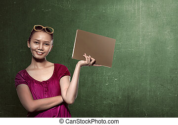 Asian female student holding book with chalkboard background