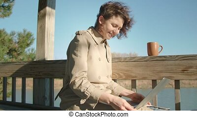 Woman sits on the bench surfs the internet with laptop. Smile.