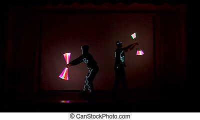 Men twist fiery circles on a LED show. - Two men rotates LED...