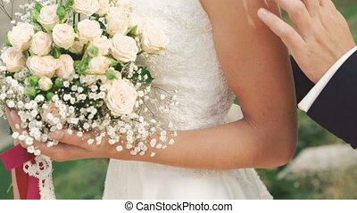 Wedding bouquet in bride's hands. Groom touching bride. 4K.