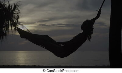 Woman on the hammock at the beach - Silhouette of young...