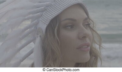 Woman with white feather indian hat at the beach - Closeup...
