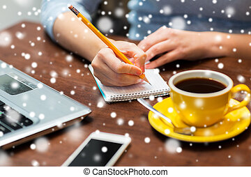 woman writing to notebook with pencil at office - business,...