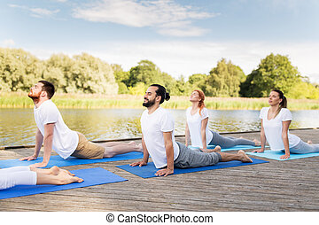 group of people making yoga exercises outdoors - yoga,...