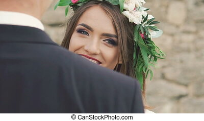 Bride comes to groom, smiling and looking into eyes. Slowly