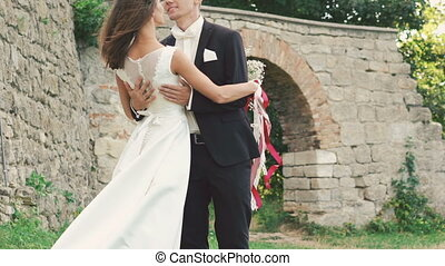 Bride and groom standing in embraces in park near the castle. Slowly