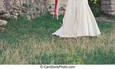 Bride in wreath wakling with bouquet near the castle....